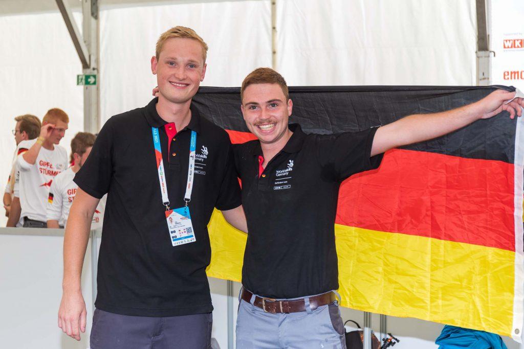 Erfolg der deutschen Fliesen-Nationalmannschaft - Yannic Schlachter hält die Deutschlandfahne zum Sieg hoch.